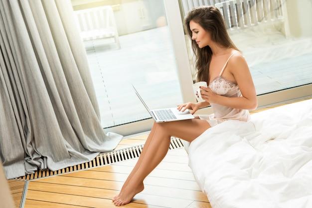 Mulher jovem e bonita usando laptop e tomando café