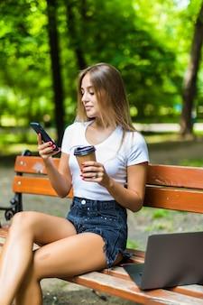 Mulher jovem e bonita usando laptop enquanto está sentado em um banco, bebendo a xícara de café para viagem