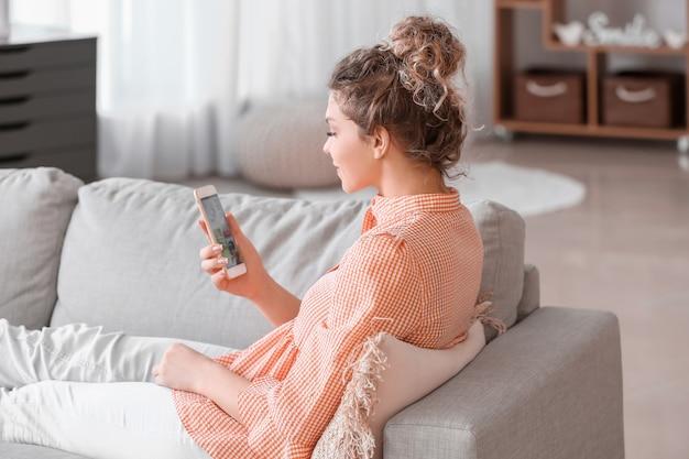 Mulher jovem e bonita usando o celular para fazer compras online em casa
