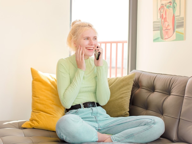 Mulher jovem e bonita usando o telefone em casa