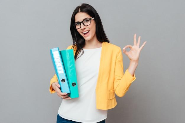 Mulher jovem e bonita usando óculos e vestida com uma jaqueta amarela, segurando pastas e fazer o gesto certo sobre a superfície cinza.