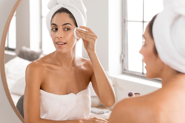 Mulher jovem e bonita usando produtos de spa em casa