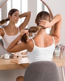 Mulher jovem e bonita usando produtos e se olhando no espelho