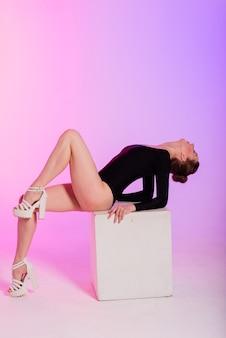 Mulher jovem e bonita usando sapatos de salto alto sexy e roupas pretas enquanto dançava em um estúdio de pole dance