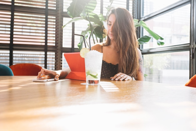 Mulher jovem e bonita usando telefone celular com copo de coquetel na mesa de madeira