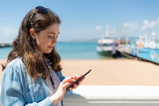 Mulher jovem e bonita usando telefone celular.