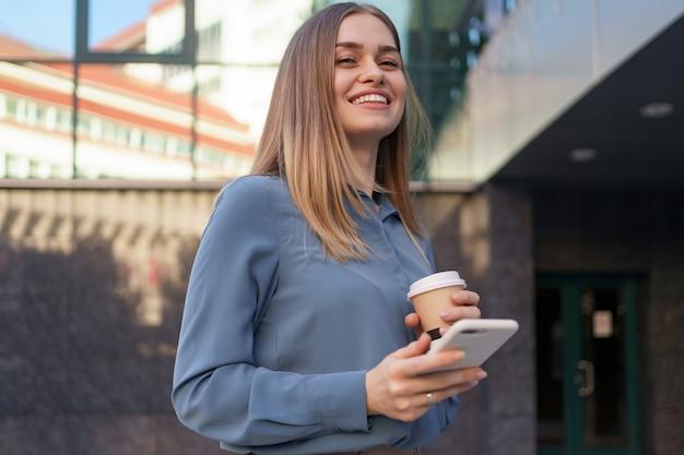 Mulher jovem e bonita usando um aplicativo em seu smartphone para enviar uma mensagem de texto perto de edifícios comerciais
