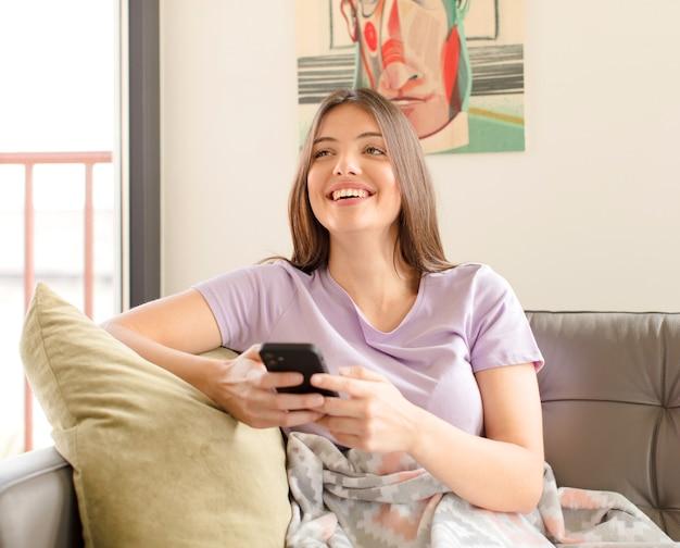 Mulher jovem e bonita usando um smartphone em casa