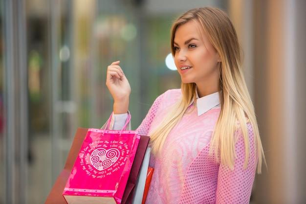 Mulher jovem e bonita vai às compras no shopping