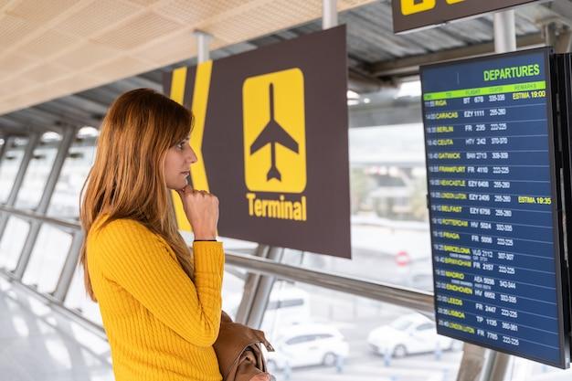 Mulher jovem e bonita verificando a hora de partida do seu voo nas placas de informações no aeroporto com sua bagagem