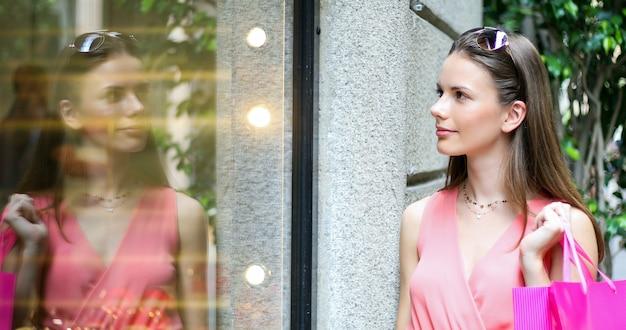 Mulher jovem e bonita verificando uma loja ao ar livre em um cenário de cidade moderna