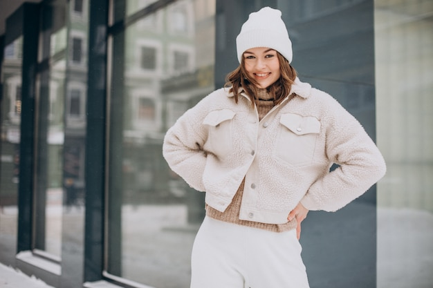 Mulher jovem e bonita vestida de bege andando na rua no inverno