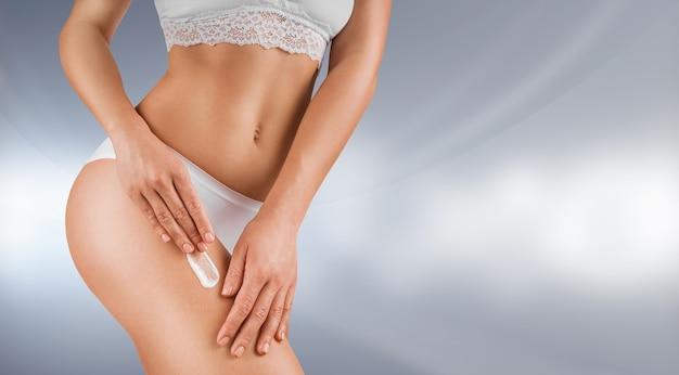 Mulher jovem e bonita vestida de cueca branca, aplicando creme corporal na pele brilhante. conceito de cuidados corporais ou cosmetologia.