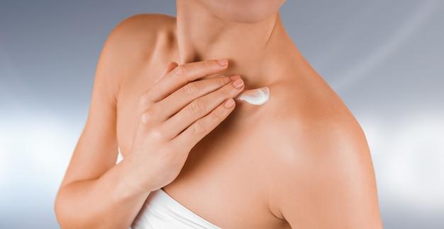 Mulher jovem e bonita vestida de cueca branca, aplicando creme corporal na pele brilhante. conceitos de cuidado corporal ou cosmetologia.