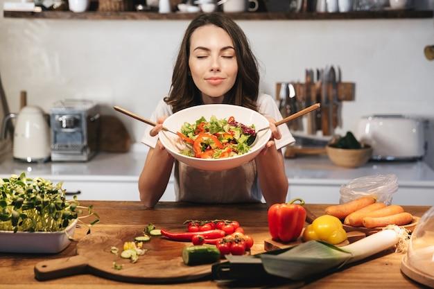 Mulher jovem e bonita vestindo avental cozinhando salada saudável na cozinha em casa, misturando