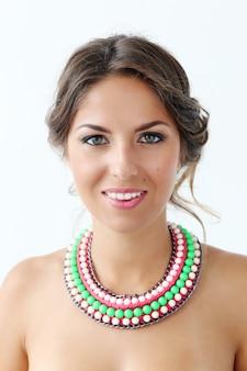 Mulher jovem e bonita vestindo colar colorido e sorrindo