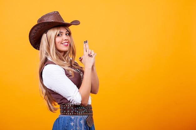 Mulher jovem e bonita vestindo fantasia de cowboy sobre fundo amarelo. momento bobo