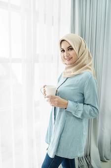 Mulher jovem e bonita vestindo hijab bebendo uma xícara de chá enquanto