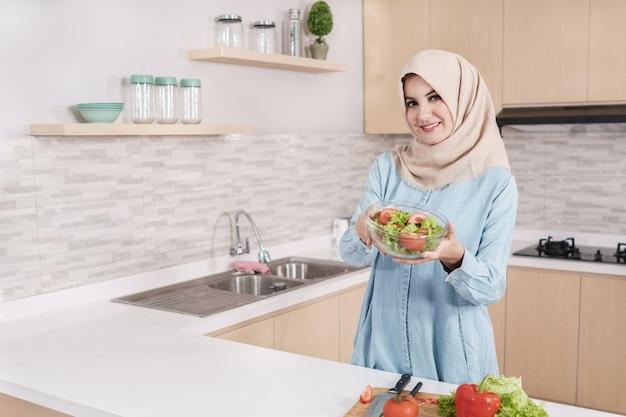 Mulher jovem e bonita vestindo hijab preparando salada de legumes em latop