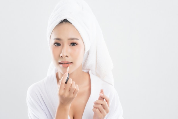 Mulher jovem e bonita vestindo roupão com toalha com toalha na cabeça está usando batom para colocar na boca após terminar a maquiagem isolada no branco.