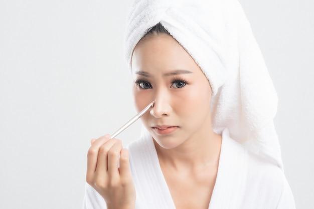 Mulher jovem e bonita vestindo roupão de banho com toalha com toalha na cabeça está usando um pincel de maquiagem maquie-a após o banho