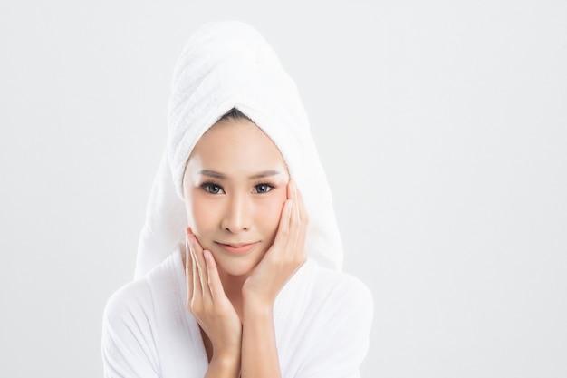 Mulher jovem e bonita vestindo roupão de banho com toalha na cabeça e pele saudável tocando sua pele