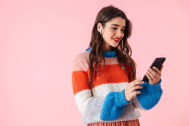 Mulher jovem e bonita vestindo roupas coloridas em pé isolado sobre o rosa, ouvindo música com fones de ouvido, segurando o telefone celular