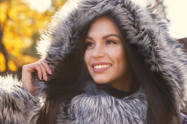 Mulher jovem e bonita vestindo um casaco com capuz de pele ao ar livre