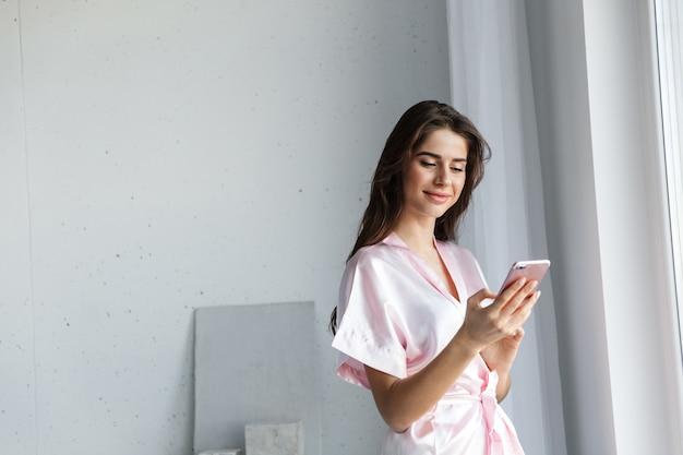 Mulher jovem e bonita vestindo um manto em pé na janela do quarto, falando no celular