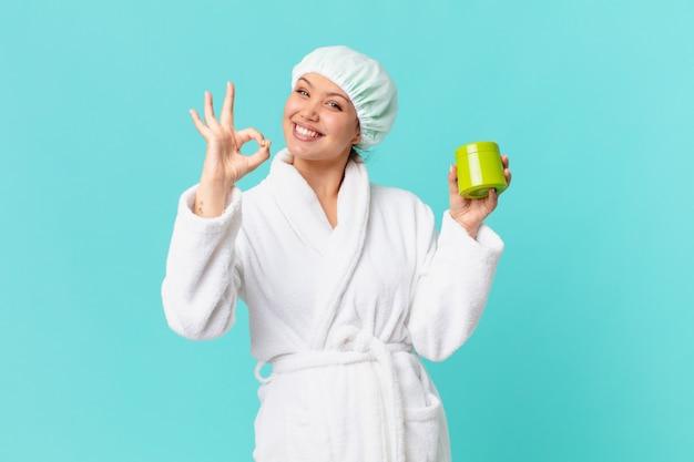 Mulher jovem e bonita vestindo um roupão de banho e segurando uma garrafa de produto limpa