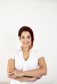 Mulher jovem e bonita vestindo uma blusa branca, sorrindo e olhando para a câmera