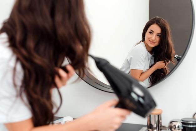 Mulher jovem e bonita vestindo uma camiseta branca, olhando no espelho secando o cabelo dela sorrindo, cabelo ventoso. foto do conceito de beleza, estilo de vida