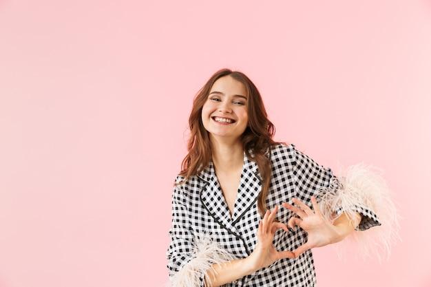Mulher jovem e bonita vestindo uma jaqueta isolada sobre um fundo rosa, mostrando um gesto de coração