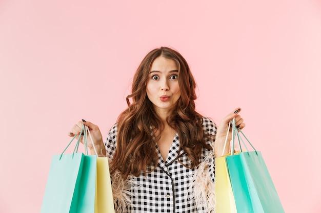 Mulher jovem e bonita vestindo uma jaqueta isolada sobre um fundo rosa, segurando sacolas de compras