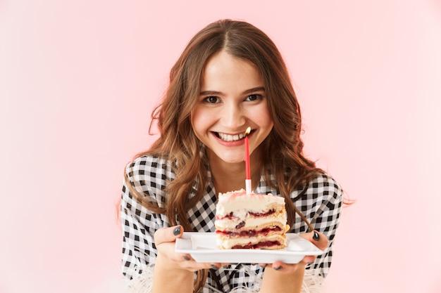 Mulher jovem e bonita vestindo uma jaqueta isolada sobre um fundo rosa, segurando um bolo de aniversário
