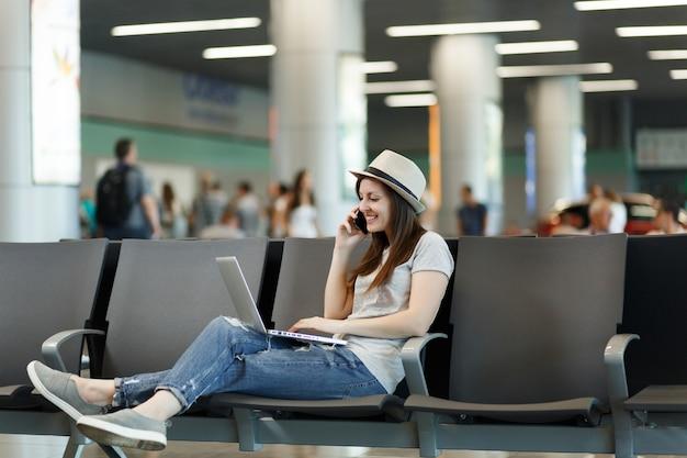 Mulher jovem e bonita viajante trabalhando em um laptop, fala no celular, liga para um amigo, reserva um táxi, espera no hotel no saguão do aeroporto