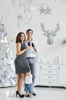 Mulher jovem e bonito, posando com seu filho pequeno bonito no interior decorado para o natal. jovens pais e filho pequeno comemorando o ano novo