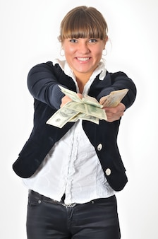 Mulher jovem e branca, branca, morena, vestindo calça preta e blusa branca, posando com notas de cem dólares