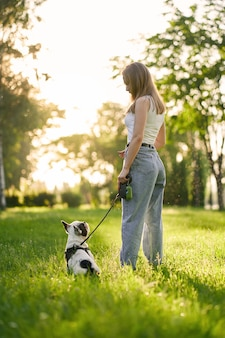Mulher jovem e buldogue francês no parque