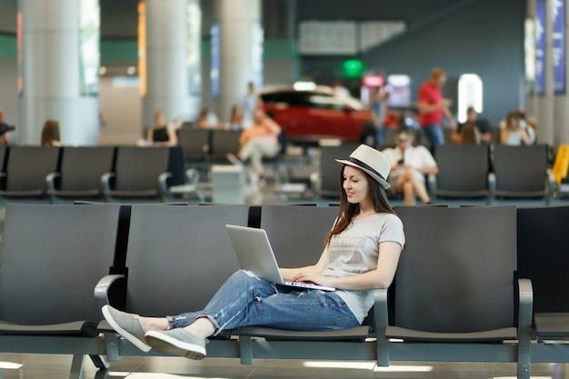 Mulher jovem e calma turista com chapéu trabalhando em um laptop enquanto espera no saguão do aeroporto internacional