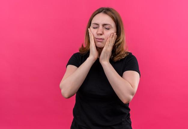 Mulher jovem e casual desapontada colocando as mãos nas bochechas com os olhos fechados em um espaço rosa isolado com espaço de cópia