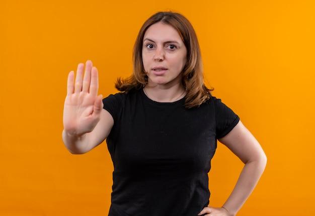 Mulher jovem e casual descontente gesticulando para parar com a mão na cintura em uma parede laranja isolada