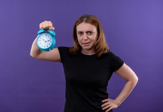 Mulher jovem e casual descontente segurando o despertador com a mão na cintura na parede roxa isolada