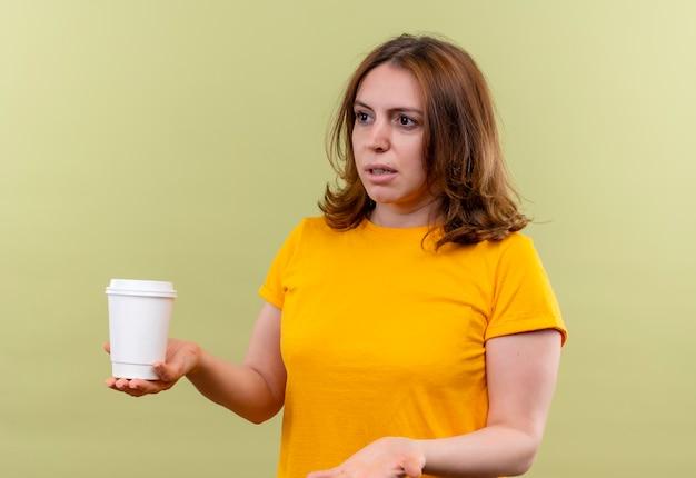 Mulher jovem e casual descontente segurando uma xícara de café de plástico e mostrando a mão vazia na parede verde isolada