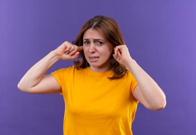 Mulher jovem e casual irritada colocando os dedos nas orelhas em um espaço roxo isolado