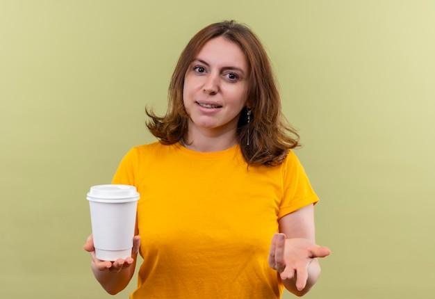 Mulher jovem e casual satisfeita segurando uma xícara de café de plástico e mostrando a mão vazia em um espaço verde isolado com espaço de cópia