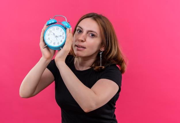 Mulher jovem e casual segurando o despertador e na parede rosa isolada com espaço de cópia
