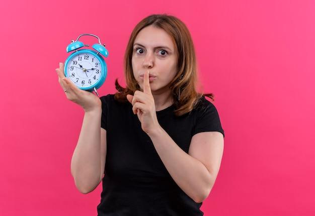 Mulher jovem e casual segurando um despertador e gesticulando para o silêncio na parede rosa isolada com espaço de cópia