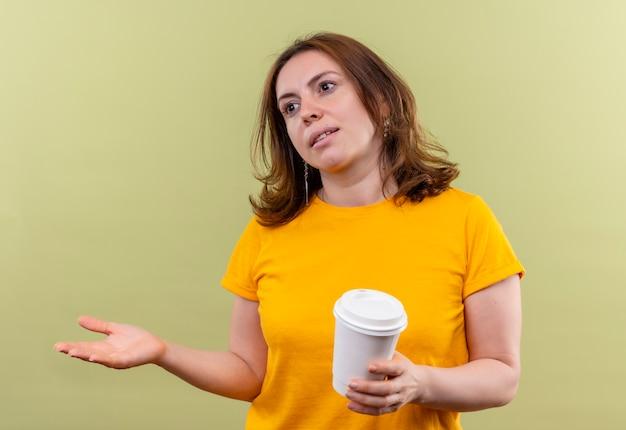 Mulher jovem e casual segurando uma xícara de café de plástico e mostrando a mão vazia, olhando para o lado esquerdo em uma parede verde isolada