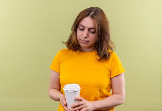 Mulher jovem e casual segurando uma xícara de café de plástico e olhando para ela na parede verde isolada com espaço de cópia